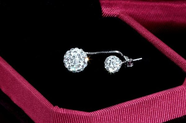 hanging silver earring with cubic zirconia stones photographed on red background in black box