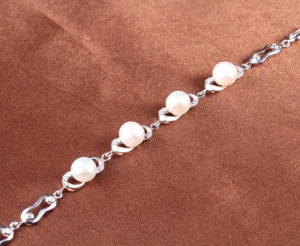 сребърна гривна с перли и кубичен цирконий снимана отгоре с перлите