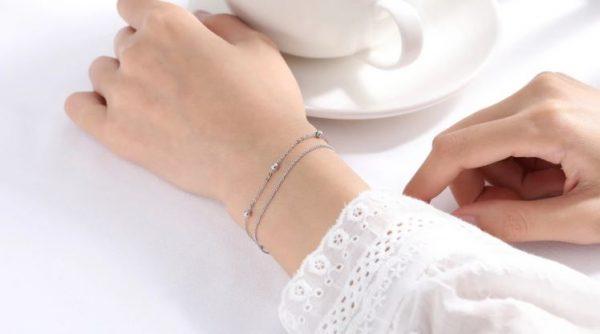 двойна сребърна гривна вержика с топчета на женска ръка и бяла чаша