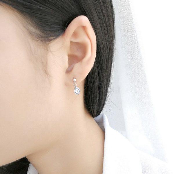 висящи сребърни обеци с кубичен цирконий и син цвят снимани на женско ухо