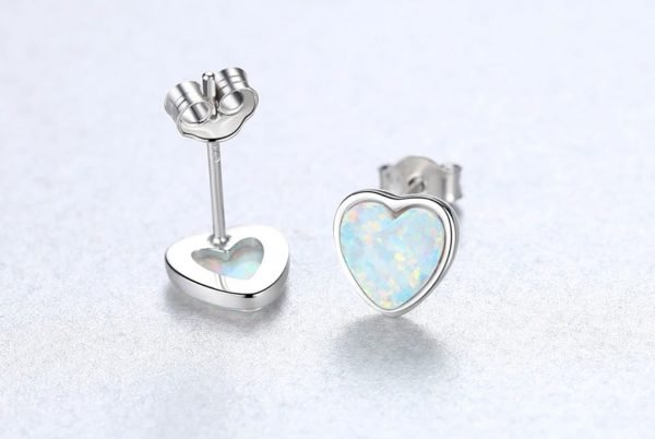 front and back of silver screw earrings in the shape of hearts with light synthetic opal