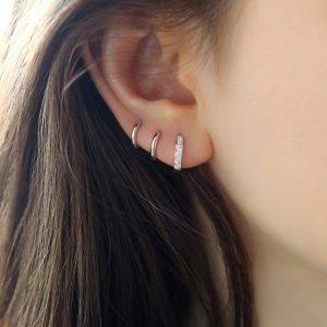 сребърни обеци напластяване снимани на женско ухо под ъгъл