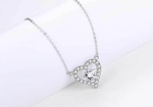 silver necklace in the shape of a heart with a cubic zirconia star in the middle of the heart photographed at an angle from the left