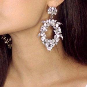 сребърни обеци тип стейтмънт снимани на женско ухо под ъгъл