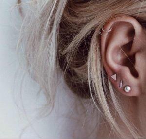 напластяване на сребърни обеци пет на брой снимани на женско ухо на момиче с руса коса