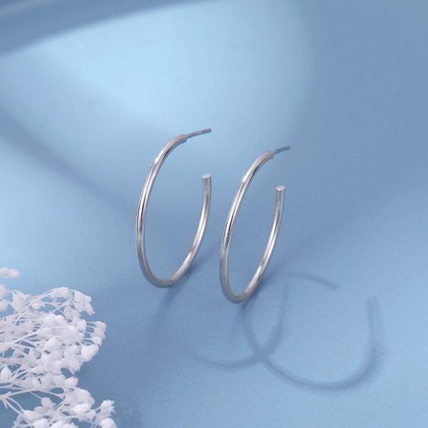 сребърни обеци халки от метал сребро 925 тип халки снимани на син фон с бяла окраска