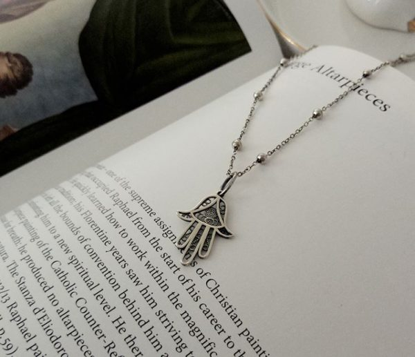 silver hamsa necklace with charm amulet photographed on book in english