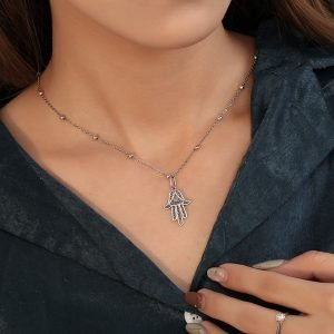 silver hamsa necklace photographed on a woman's neck