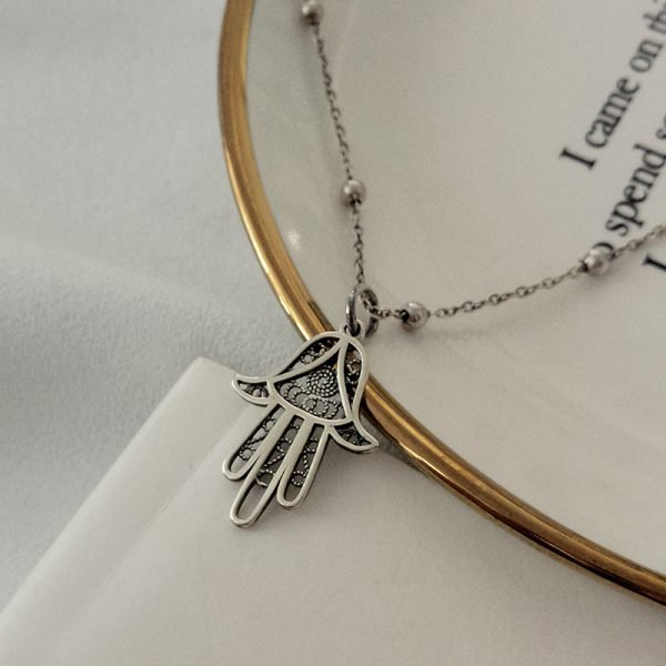 925 silver hamsa necklace with hamsa amulet photographed on white plate