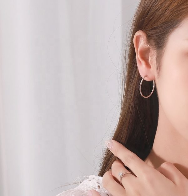 сребърна обеца тип халка снимана на модел жена