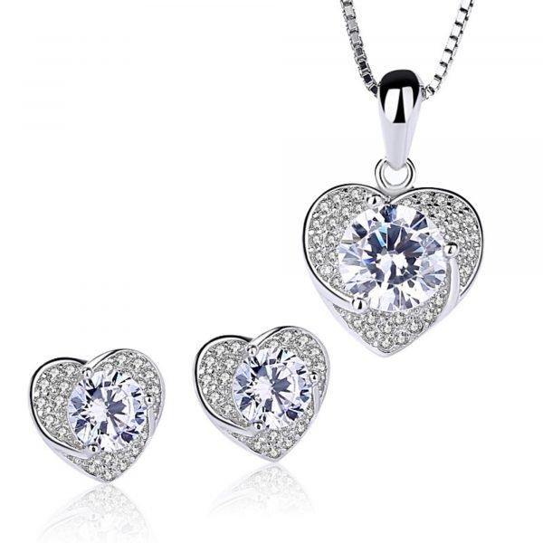 сребърен комплект любов състоящ се от колие и обеци в сърцевидна форма и множество камъчета кубичен цирконий на бял фон