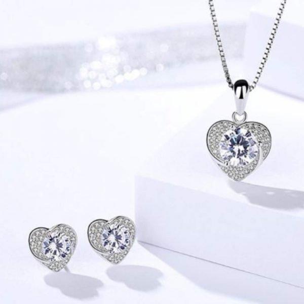 сребърен комплект любов състоящ се от колие и обеци в сърцевидна форма и множество камъчета кубичен цирконий снимани под ъгъл