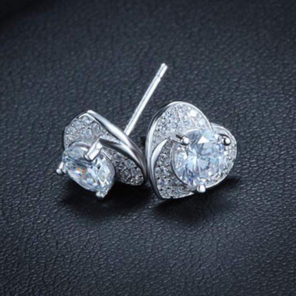 обеците от сребърен комплект любов състоящ се от колие и обеци в сърцевидна форма и множество камъчета кубичен цирконий снимани на черен фон