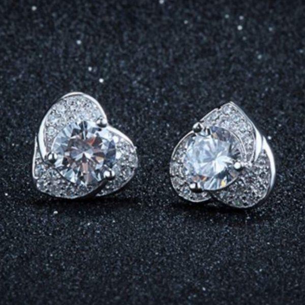 обеците от сребърен комплект любов състоящ се от колие и обеци в сърцевидна форма и множество камъчета кубичен цирконий снимани централно на тъмен фон