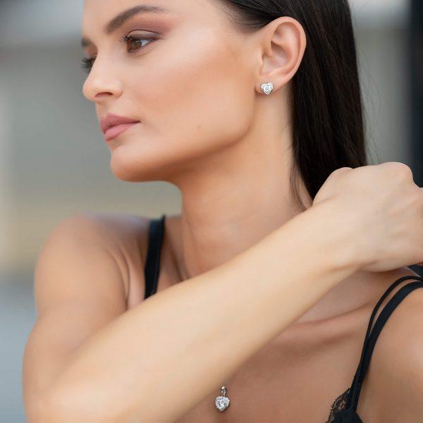 сребърен комплект любов състоящ се от колие и обеци в сърцевидна форма и множество камъчета кубичен цирконий сниман отстрани на красива жена модел