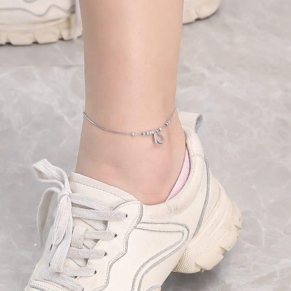сребърна гривна за глезен сърце с мънисто на женски крак с бели обувки