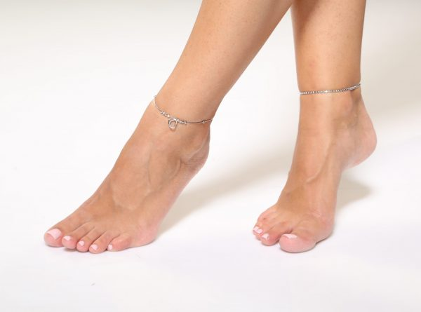 Две сребърни гривни за крак снимани на бял фон върху глезените на модел