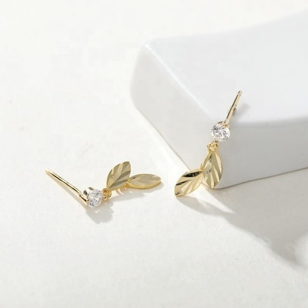 silver-gold earrings in the shape of feathers