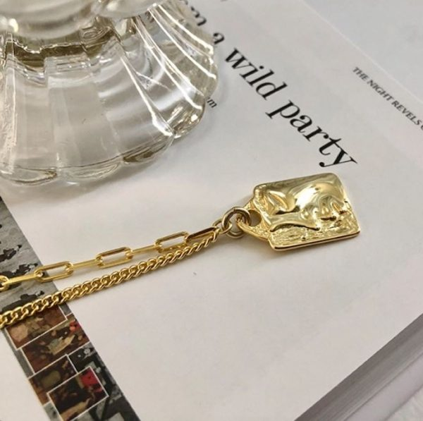 Gilded silver plate necklace with a face on it, placed on a book page