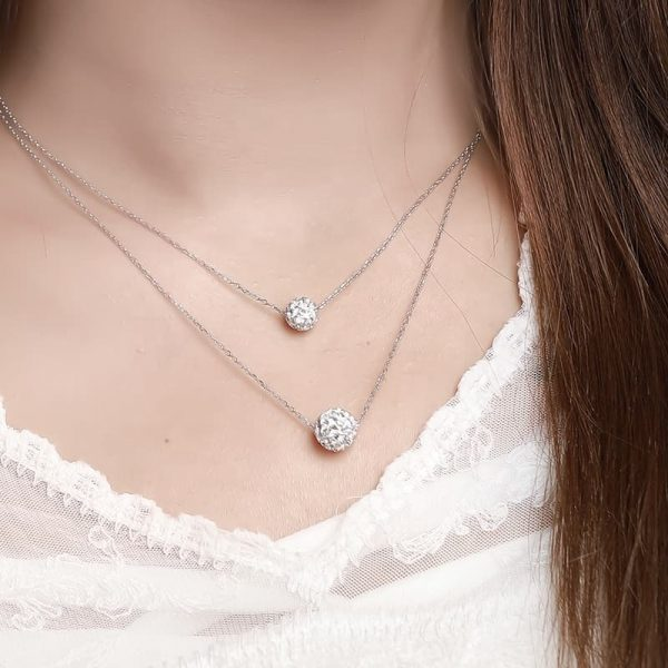 Double silver necklace with oval elements covered with cubic zirconia photographed on a model at a slight angle
