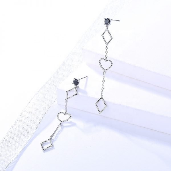 Product photography of hanging silver earrings with two diamonds at the top and bottom and a heart in the middle on a white background