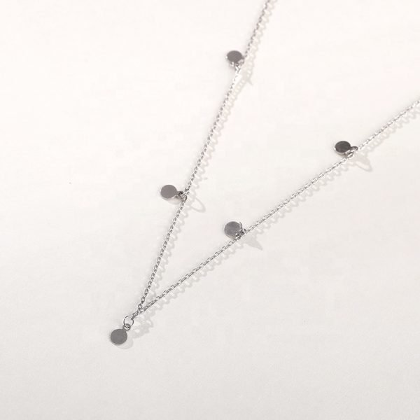 Clear silver necklace with five oval charms photographed from above on a white background
