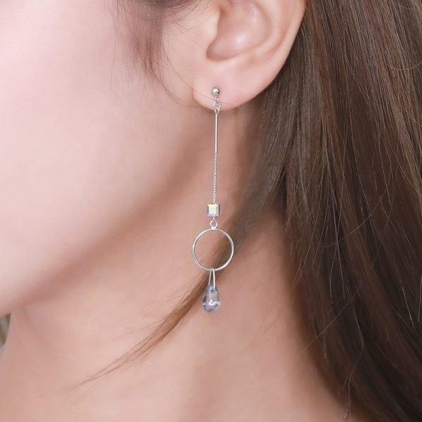 Висящи сребърни обеци с два кристала и халка посредата снимани на женско ухо