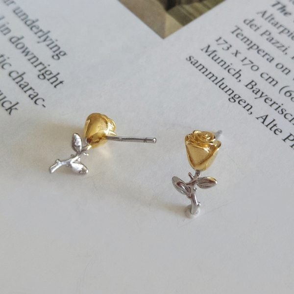 silver earrings in the form of an eternal rose with 18 carat gold plating on a page from a book with a screw accent