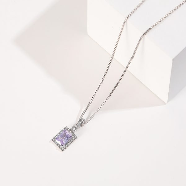 silver necklace with Venetian braid and purple cubic zirconia photographed from an angle in close-up on a white background