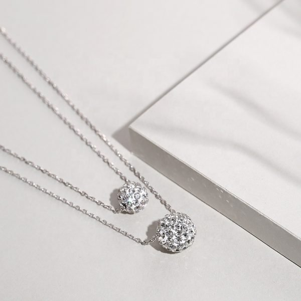 Close-up photo from a slight angle of a double silver necklace with oval elements covered with cubic zirconia