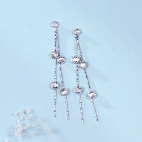 frontal photo of hanging silver earrings with 10 cubic zirconia stones on blue surface