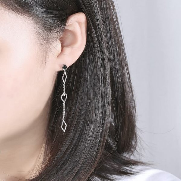 Hanging silver earrings with two diamonds at the top and bottom and a heart in the middle of a woman's ear at an angle
