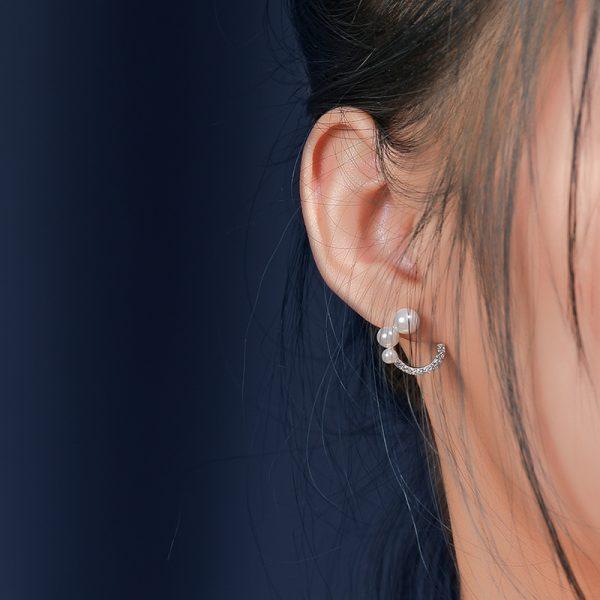 Сребърни обеци с три перли и кубичен цирконий снимани на женско ухо под лек ъгъл