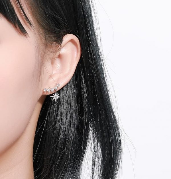 shiny silver earring with cubic zirconia crawling on the ear with a star-shaped ornament photographed on a woman's ear