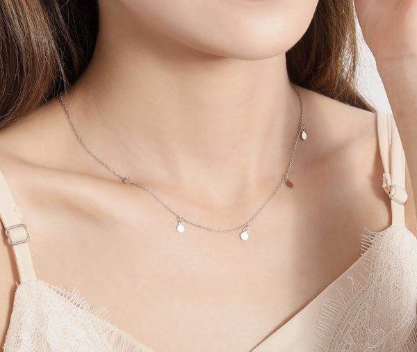 Clear sterling silver necklace with five oval charms photographed on a close-up model