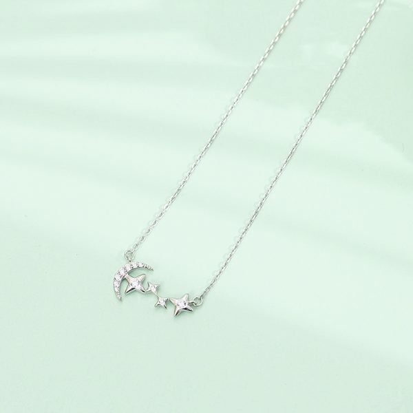 Silver necklace with half moon and four stars forming a constellation photographed on a nice greenish background