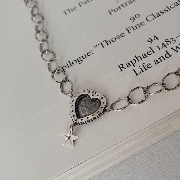Сребърно колие тип чокър с масивно сърце и по-малка звезда под него снимано от задната страна на медальона върху страница от книга
