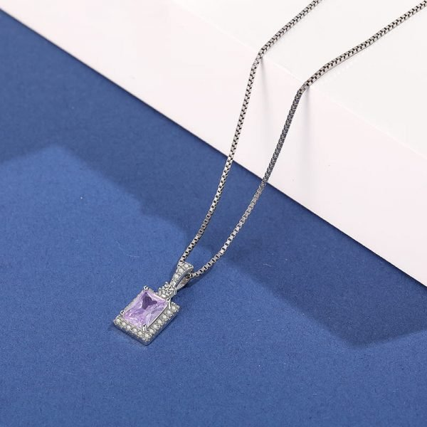 silver necklace with Venetian braid and purple cubic zirconia photographed from a slight angle in close-up on a blue-white background