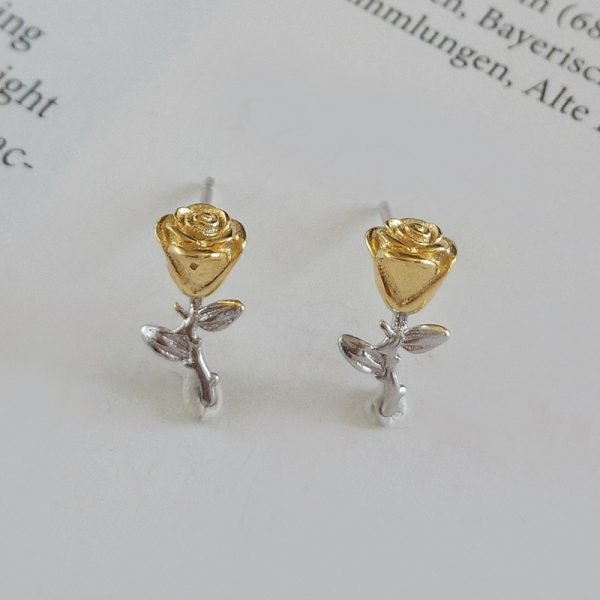 silver earrings in the shape of an eternal rose with 18 carat gold plating photographed at a slight angle on a page from a book