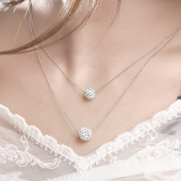 Double silver necklace with oval elements covered with cubic zirconia photographed on a model