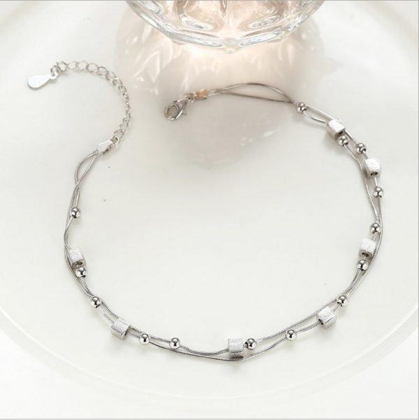 продуктова фотография на двойна сребърна гривна за крак с преплетена верижка, мънисто и кубчета на светъл фон