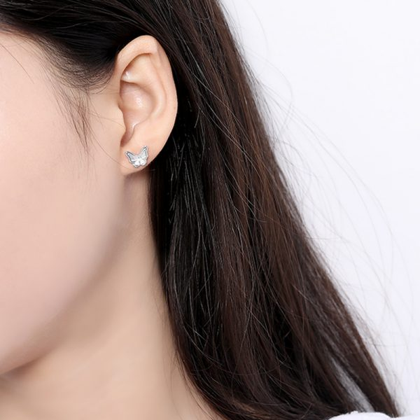 silver earring with cubic zirconia in the shape of a butterfly photographed on a woman's ear