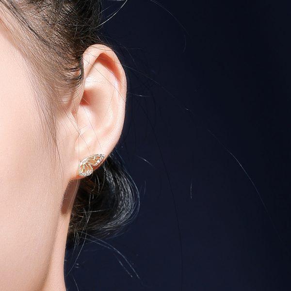 сребърна обеца под формата на крило на пеперуда снимана под ъгъл върху дамско ухо