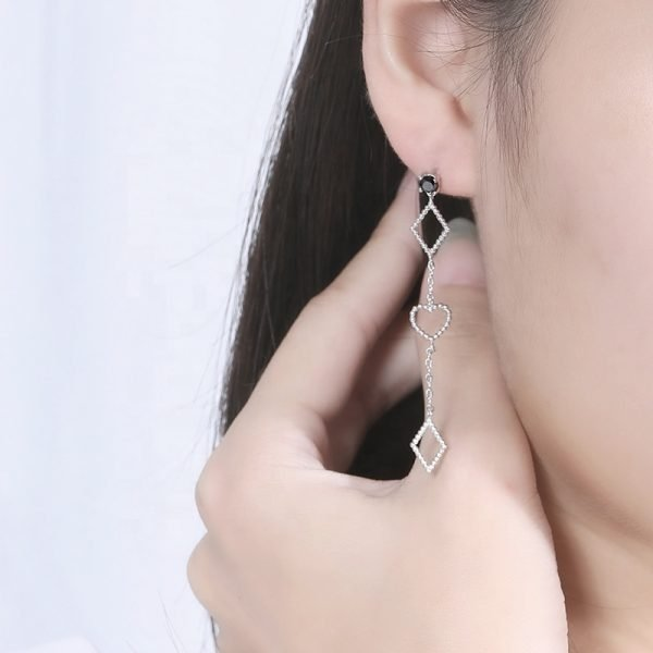 Hanging silver earrings with two diamonds at the top and bottom and a heart in the middle of a woman's ear in close-up