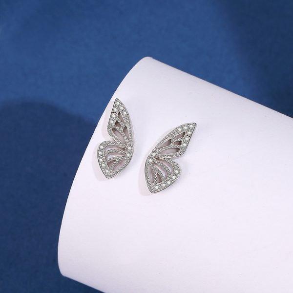 сребърни обеци под формата на пеперуда снимани централно върху бяло платно на син фон