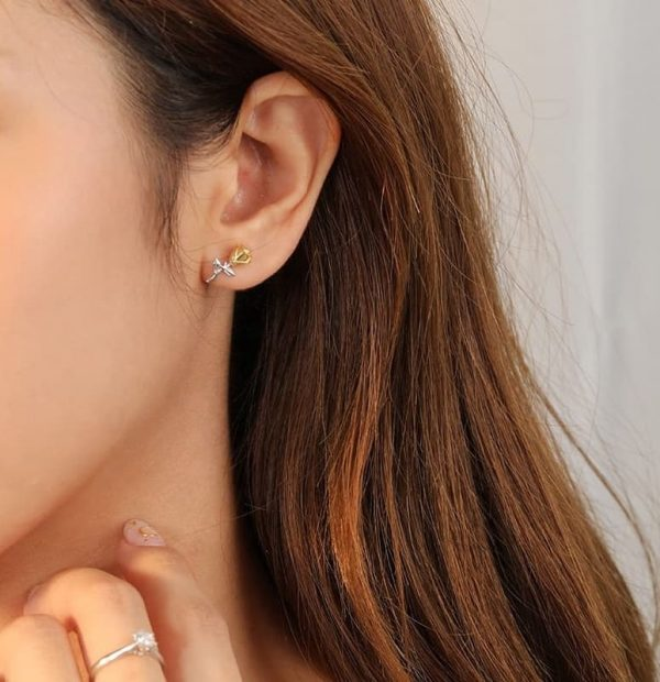 silver earring in the shape of a rose with a gold tip photographed on a woman's ear