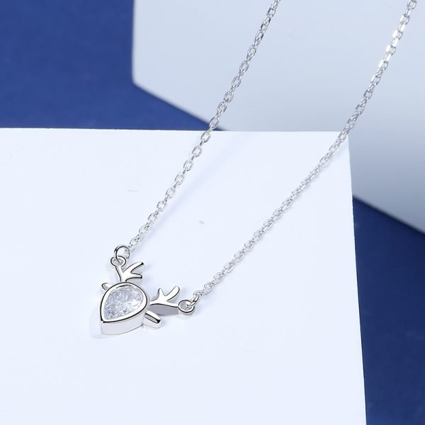 detailed photo at a slight angle of a silver necklace with a pendant in the shape of a deer with a cubic zirconia in the middle on a blue-white background