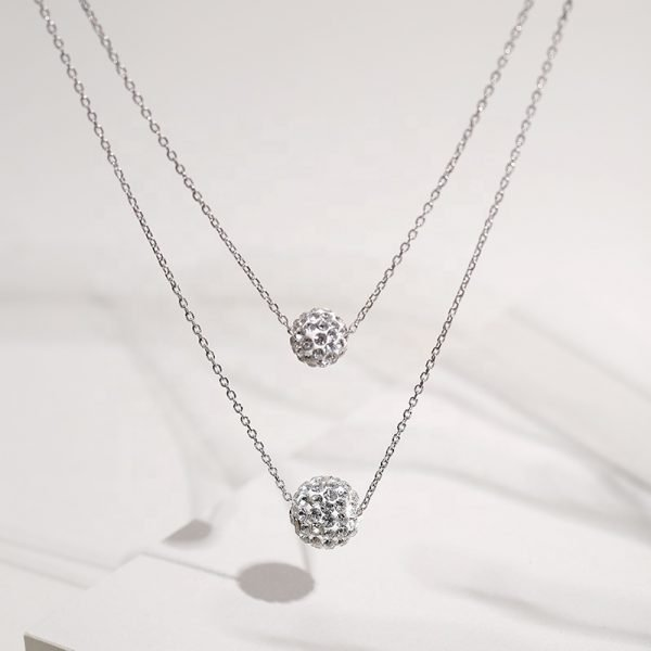 detailed frontal photo of a double silver necklace with oval elements covered with cubic zirconia on a light background