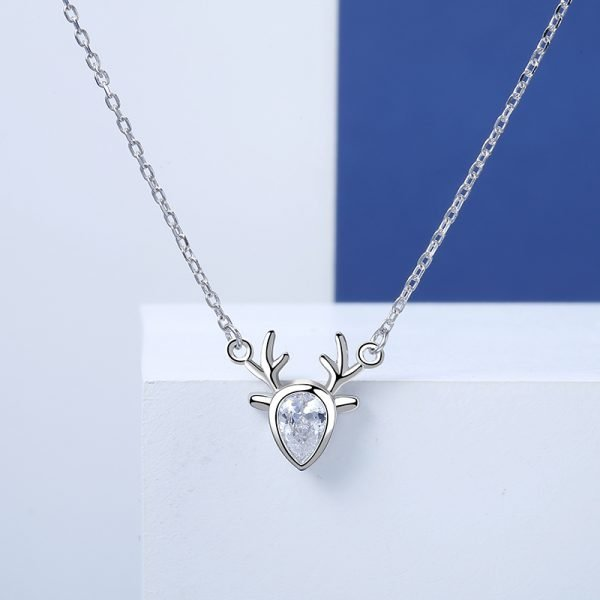 detailed frontal frame of a silver necklace with a pendant in the form of a deer with a cubic zirconia in the middle on a blue-white background