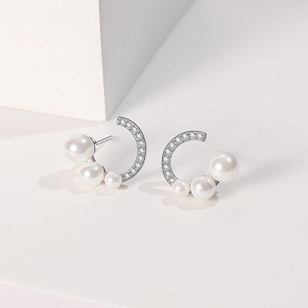 Сребърни обеци с три перли и кубичен цирконий снимани от близо на бял фон